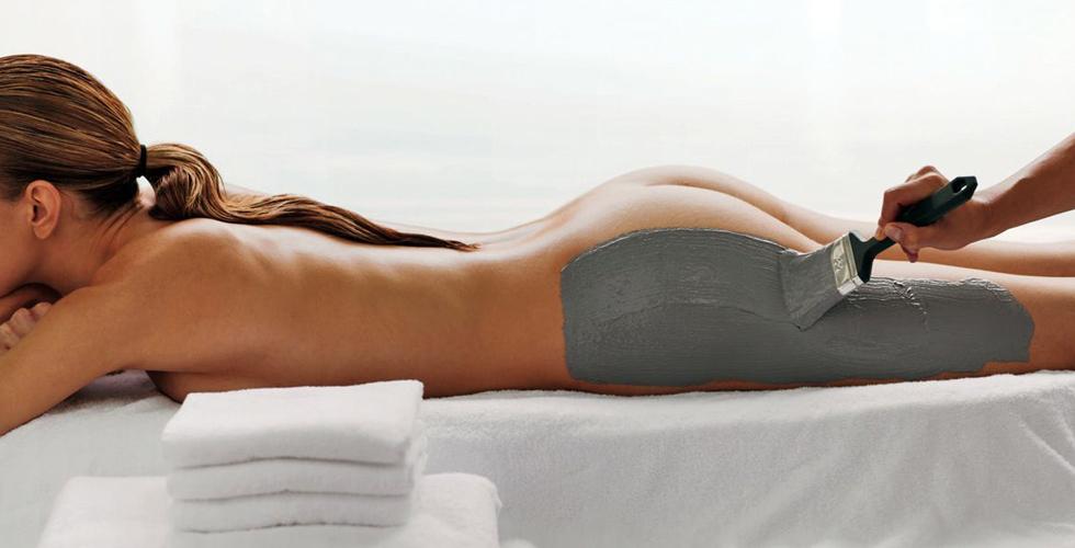 Donna sdraiata durante l'applicazione di fango anticellulite