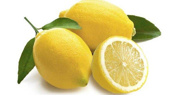 Limoni in primo piano interi e tagliati a metà su sfondo bianco