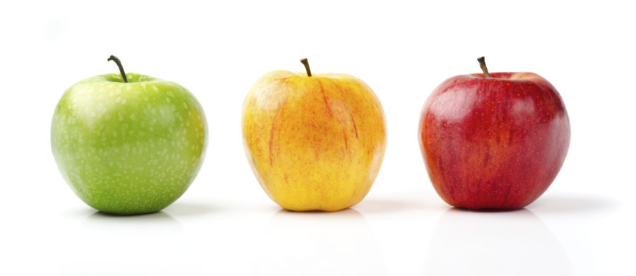 Mela verde, mela gialla e mela rossa in primo piano, allineate, su sfondo bianco
