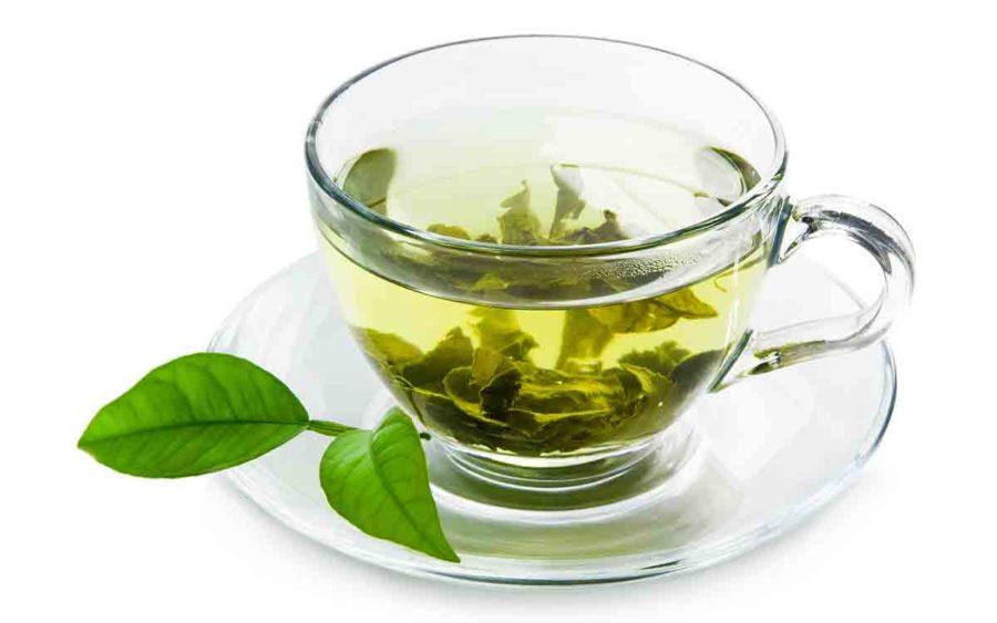 tazza trasparente di tè verde con piattino e foglie di tè
