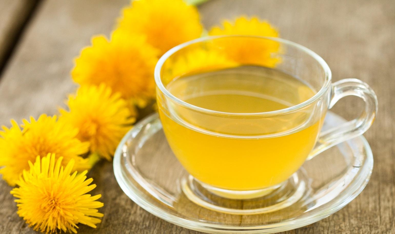 Tisana al tarassaco in tazza di vetro e fiori