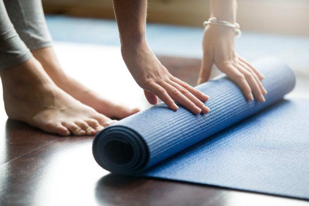 donna che sistema il tappetino di fitness