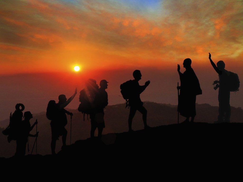 viaggiare benefici per la salute, viaggiatori salutano al tramonto in montagna