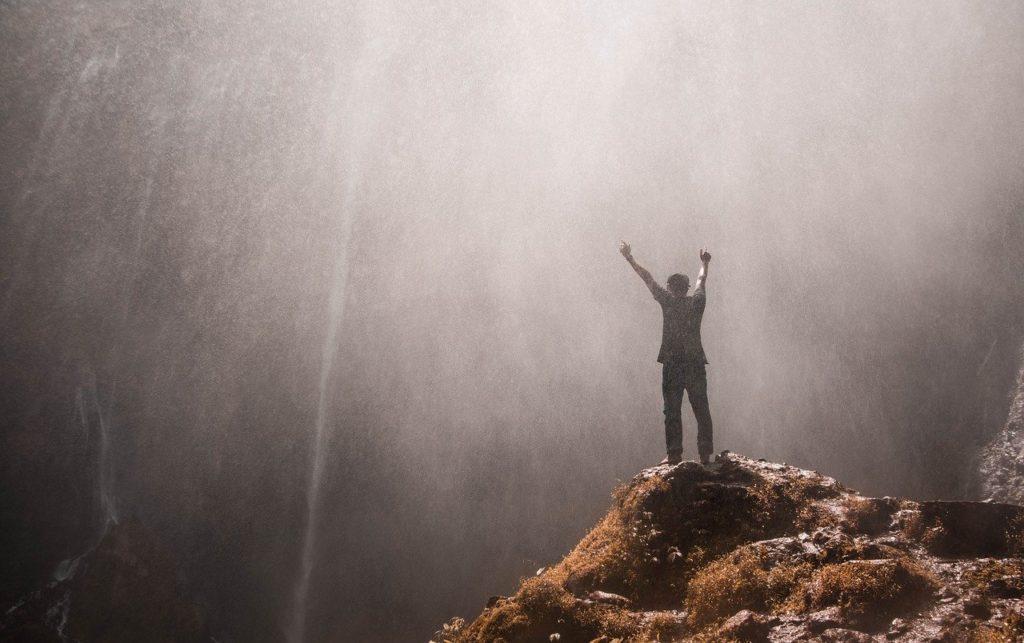 viaggiare benefici per la salute, uomo felice vicino a cascata in montagna