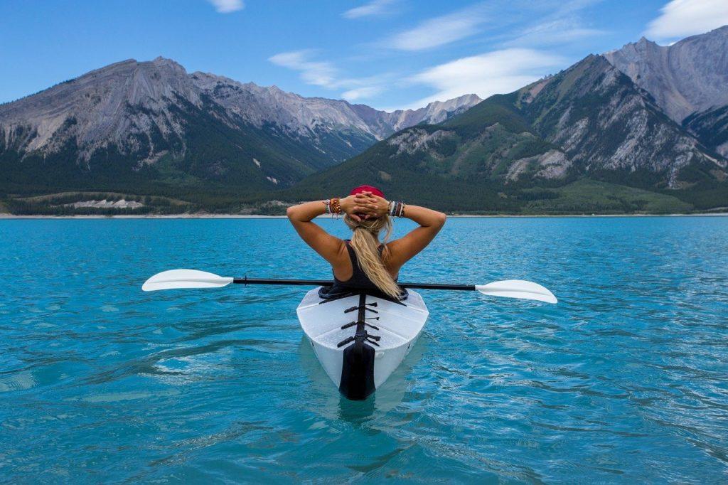 viaggiare benefici per la salute, donna relax in canoa in un lago